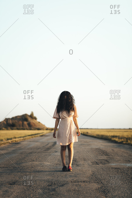 Young woman standing on country road, hiding face behind her brown hair