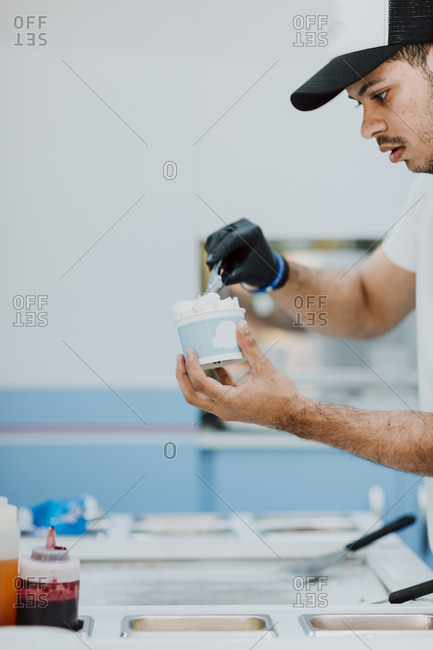Young man preparing a roll of ice in an ice cream shop