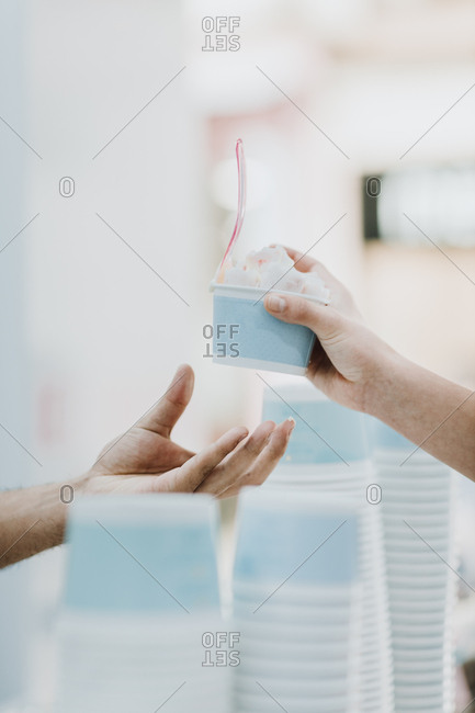 Handing over of roll of ice in an ice cream shop