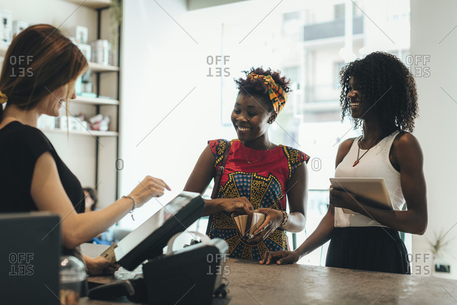 Two customers paying at counter in a coffee bar