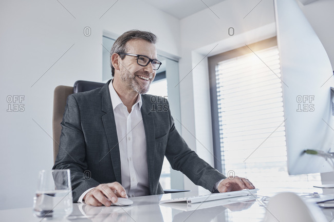 Happy businessman working at desk in office