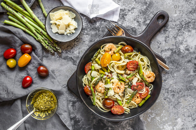 spaghetti with shrimps, green asparagus, tomato, pesto and parmesan