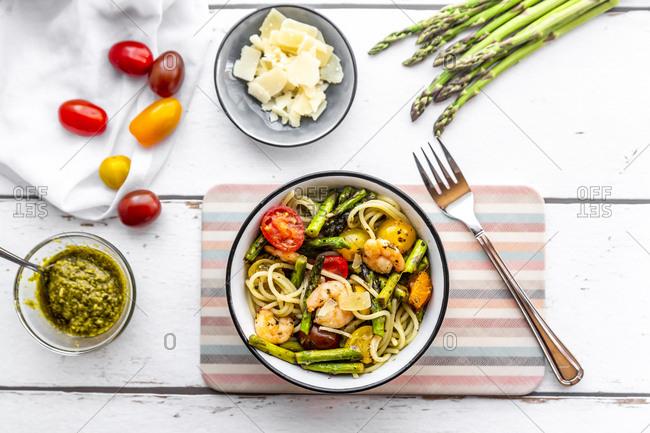 spaghetti with shrimps, green asparagus, tomato, pesto and parmesan