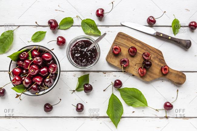 Jar of cherry jam and cherries on white wood