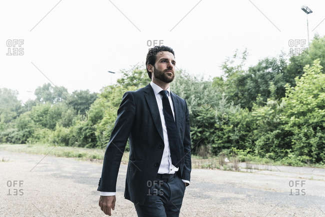 Businessman walking in remote landscape