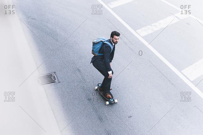 Businessman riding skateboard on the street