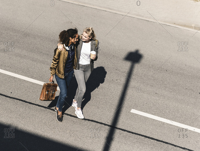Young women walking on empty road, smiling with arms around
