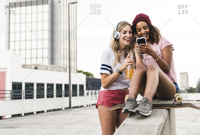 Best friends with skateboard, having fun together, listening music