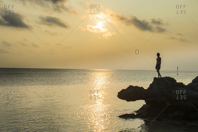 May 10, 2016: Man on a rock in backlight on the rocky west coast in Ouvea, Loyalty Islands, New Caledonia, Pacific