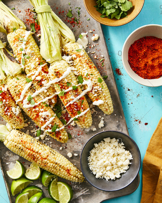 Grilled corn elote served with Mexican crema, chili powder, and lime