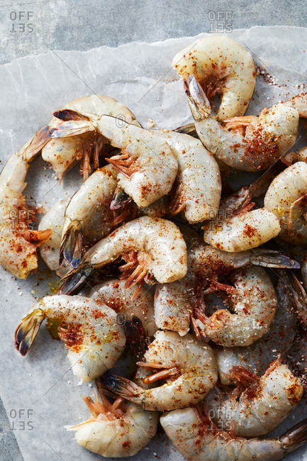 Uncooked shrimp with dry seasonings on parchment paper