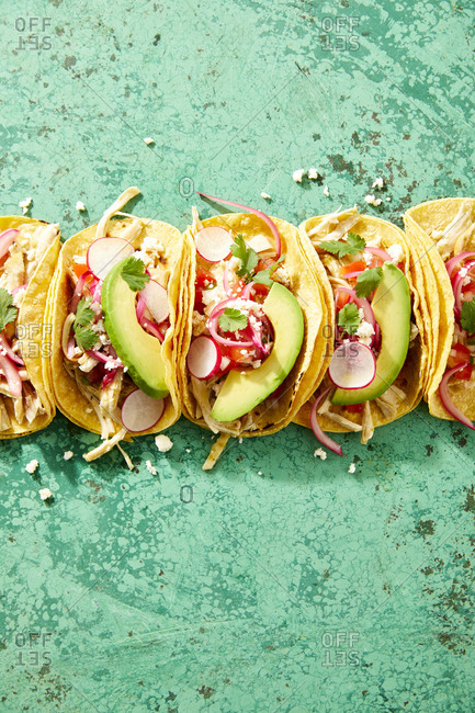 Street tacos topped with fresh radish and avocado