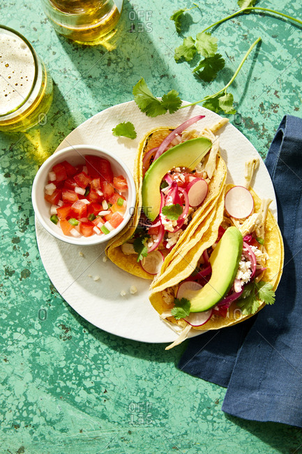 Mexican street tacos topped with fresh radish and avocado served with beer and pico de gallo