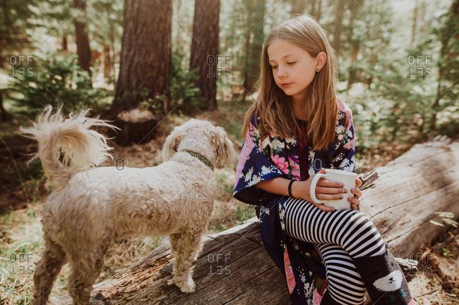 Girl sitting on log by dog