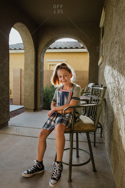 Young girl sitting on outdoor chair holding school books
