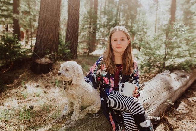 Portrait of girl sitting on log by dog