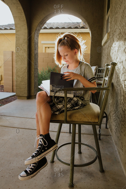 Young girl sitting on outdoor chair reading school books