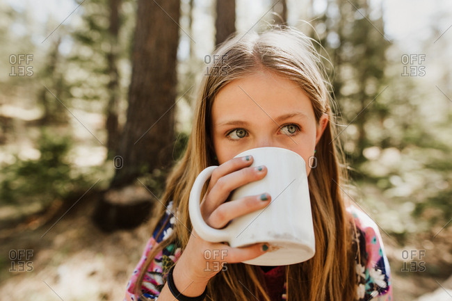 Girl sitting in woods drinking from mug