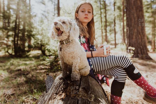 Girl sitting on log with white furry dog