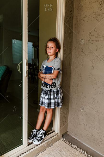 Girl standing in doorway holding school books