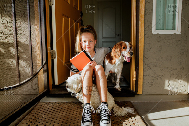 Young girl sitting in doorway with dogs holding school books