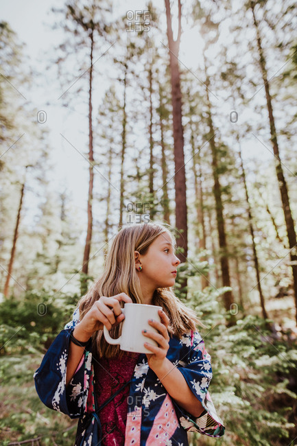 Girl in woods drinking from mug