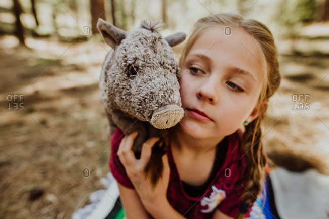 Girl sitting on blanket in woods with stuffed pig