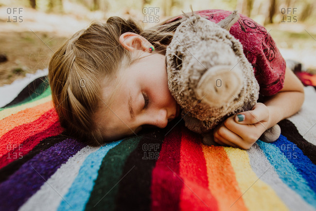 Girl lying on blanket in woods with stuffed pig