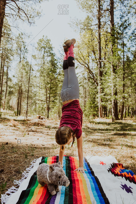Girl doing handstand on blanket in woods with stuffed pig