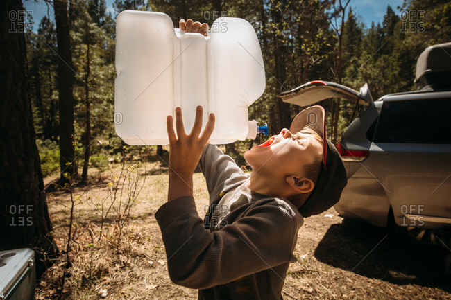 Boy drinking from water jug while camping