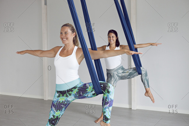 Two strong women practicing aerial yoga