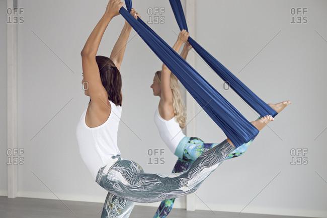 Two women practicing aerial yoga in sunlit studio