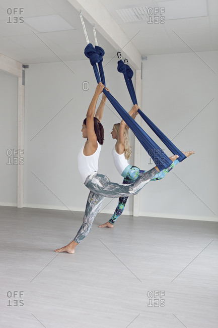 Women practicing aerial yoga next to each other