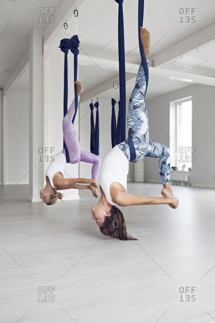 Women in yoga studio doing aerial yoga together