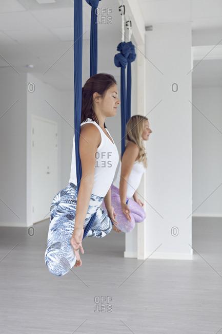 Women in yoga studio doing aerial yoga