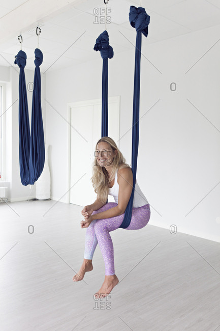 Blonde woman hanging out doing aerial yoga