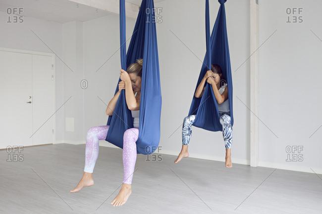 Women sitting in aerial yoga straps