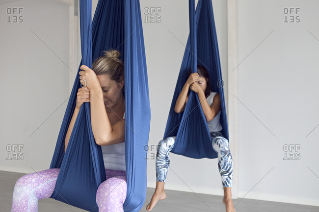 Two young women resting in yoga straps