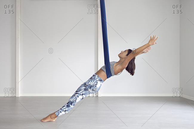 A woman stretching out using aerial yoga strap