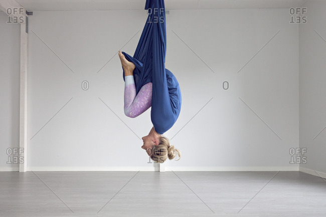 Woman laughing upside down doing aerial yoga