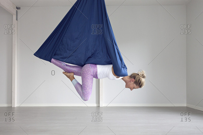 Woman hanging from aerial yoga strap