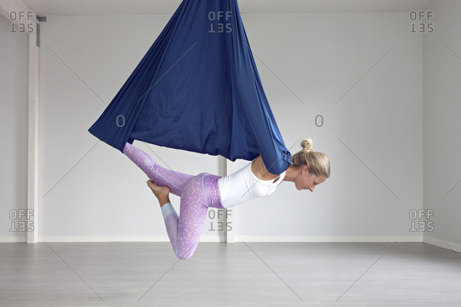 Woman holding aerial yoga posture