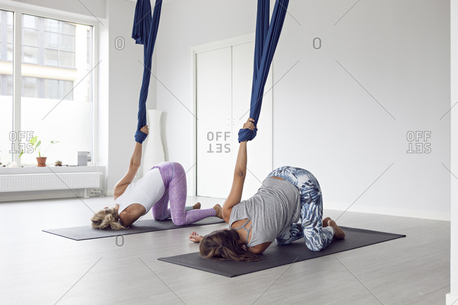 Two women doing yoga on mat with yoga strap
