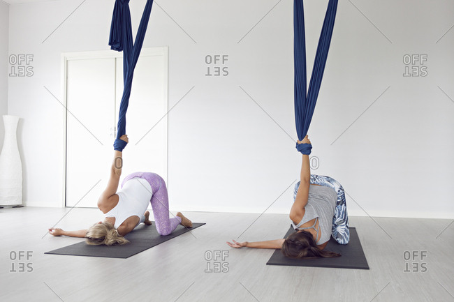 Women using yoga mats and aerial yoga strap