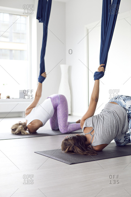 Side view of two women doing yoga with straps