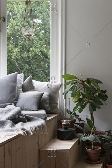Wooden window seat with cozy throw and pillows