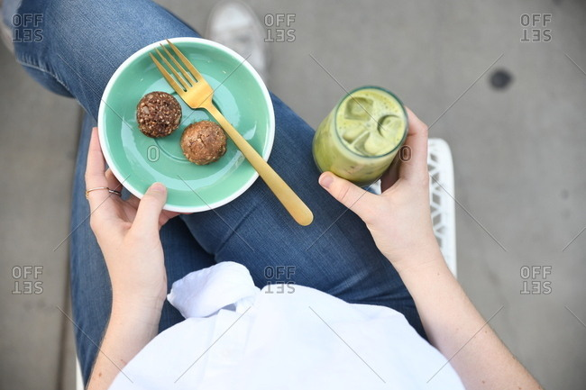Woman holding plate with energy bites and green smoothie