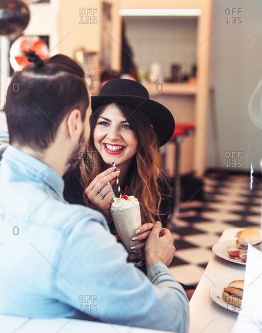 Beautiful Caucasian brunette drinking milkshake ad talking with her boyfriends at cafe