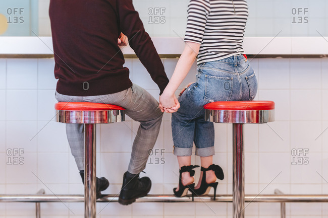 Back view of unrecognizable cropped man and woman sitting on bar chairs and holding hands at retro cafe