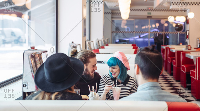 Young stylish men and women laughing at vintage diner restaurant